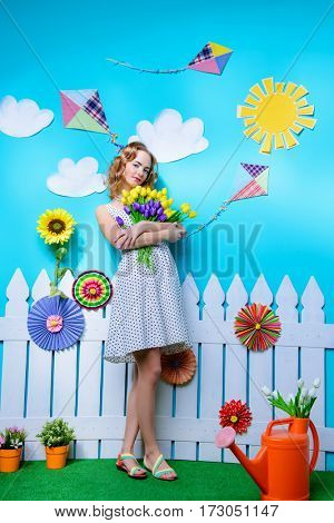 Pretty young woman with beautiful foxy hair holds a bouquet of tulips. Spring and summer holidays. Women's Day. Beauty, fashion concept.