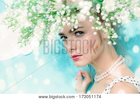 Close-up portrait of a pretty young woman wearing romantic wreath of flowers. Summer fashion. Beauty, cosmetics. Skincare.