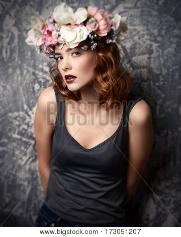 Modern young woman wearing casual clothes and wreath of flowers. Cosmetics and make-up. Spring and summer fashion.