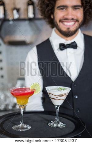 Portrait of bartender holding tray of cocktail and milkshake in bar