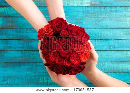 top view of hands holding roses bouquet