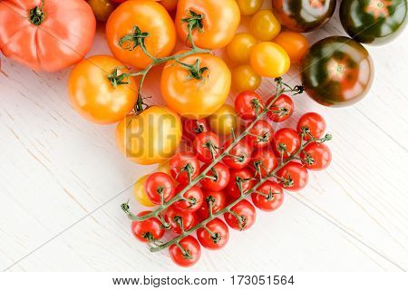 Close-up top view of various fresh ripe tomatoes on wooden table