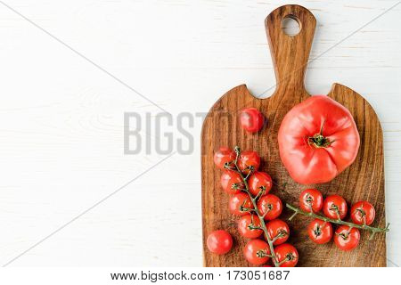 Top view of fresh tasty tomatoes on wooden cutting board