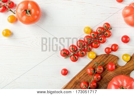 Top view of fresh red and yellow tomatoes on wooden cutting board and table