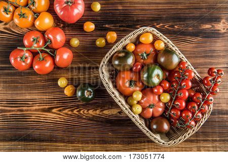 Top view of various fresh tomatoes in basket and on wooden table