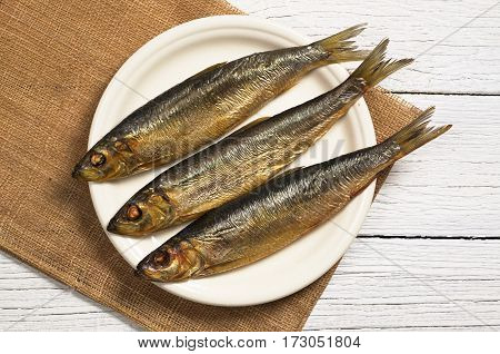 Smoked fish in plate on white wooden table top view