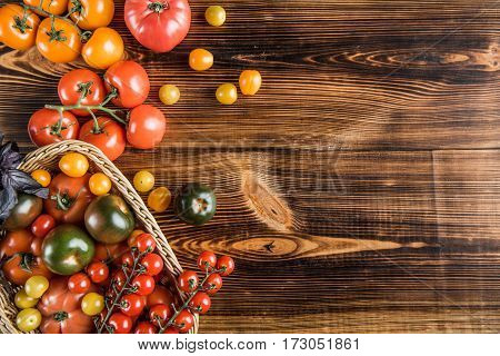 Top view of fresh ripe tomatoes in basket on wooden table