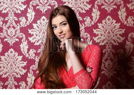 Beautiful young woman wearing evening red dress posing over vintage wallpaper. Beauty, fashion.