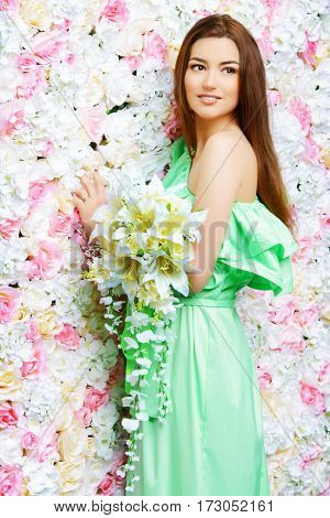 Beautiful smiling young woman in long light dress standing with a bouquet of white flowers by a floral background. The mood of the spring and summer. Beautiful smiling bride, wedding.