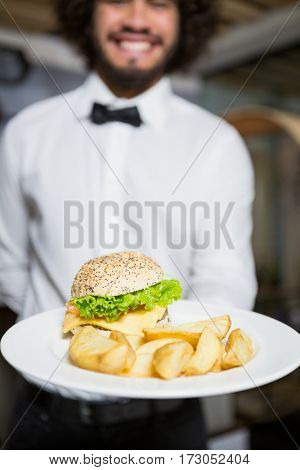 Mid section of waiter holding plates of potato chip and burger in bar