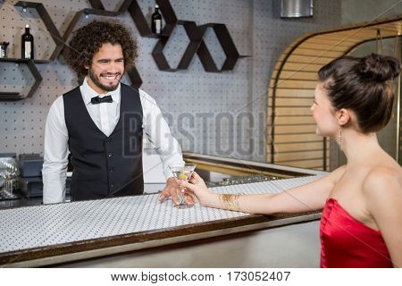 Waiter interacting with beautiful woman in bar counter