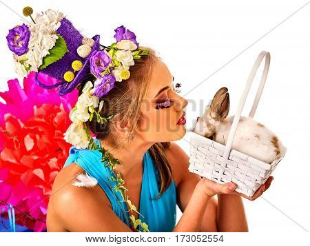 Easter dresses for women. Girl holding bunny and eggs. Woman with holiday hairstyle and make up holding rabbit in basket with flowers. Adults at festival. White background.
