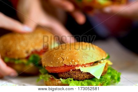 Hamburger fast food with ham on wooden board . Group of hamburger. Piece of cheese hanging from sandwich. Human hand holding cheeseburger is not in field.