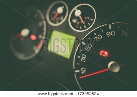 Close up shot of a car's dashboard with the battery icon lit.