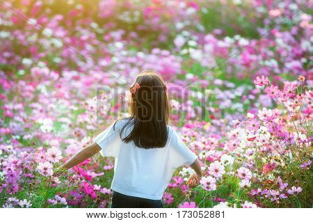 Young girl in a field smelling a pink flower - Cosmos bipinnatus.