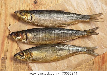 Smoked herring in paper on old wooden table close up top view