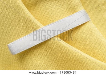 Blank clothes label on yellow cotton as a background