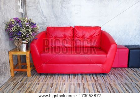 Red sofa in a room with wood tiled floors the back wall is a cement sideways put a vase of flowers.