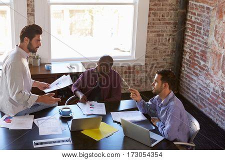 Group Of Businessmen Working Together In Boardroom