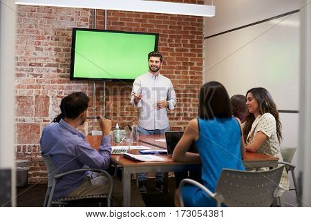 Businessman Standing By Screen To Deliver Presentation