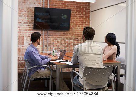 Businesspeople In Meeting Room Looking At Screen