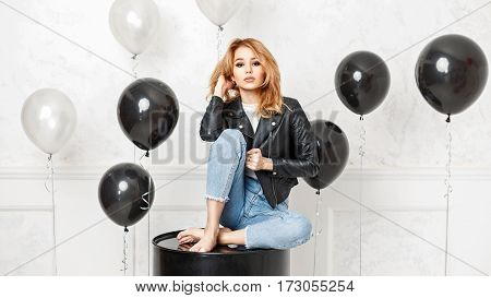 Beautiful Young Blonde Woman In A Black Jacket Sits On A Black Metal Barrel