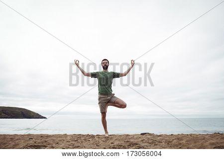 Man performing yoga on beach