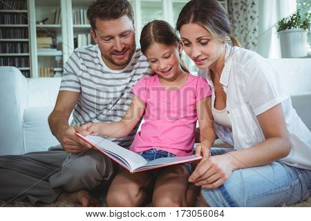 Parents and daughter sitting on the floor and looking at photo album