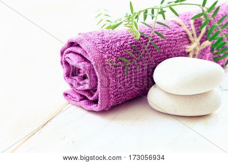 Relaxing spa background with empty space for product display. Violet bathroom towel, green plant decor, stones. Soft light.