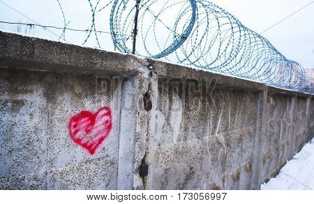red heart painted on a concrete wall against the backdrop of barbed wire the concept of a broken love relationship lonely obstacle platonic one sided