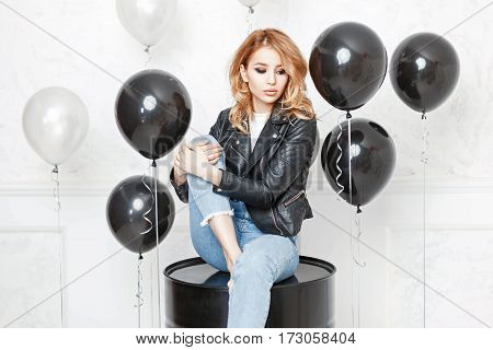 Pretty Woman In Stylish Black Leather Jacket And Blue Jeans Sitting On The Black Barrel
