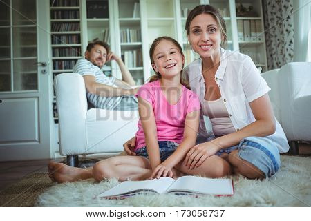 Mother and daughter looking at photo album while father sitting on sofa