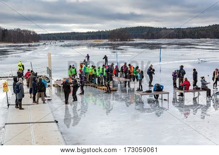 Group of ice skaters and volunteers at a rest area on the ice.Upplands Vasby, Sweden - February 19, 2017: Group of ice skaters and volunteers on melting ice lake late winter day seen from above. Participants and volunteers of the annual ice skating event