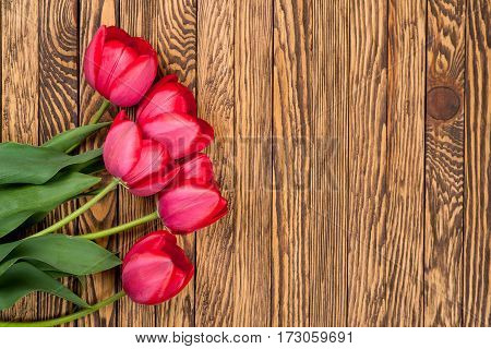 Tulips on a wooden background. Space for the text. Top view