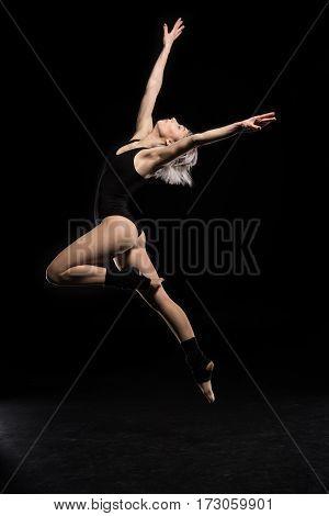 side view of dancing woman in bodysuit on black