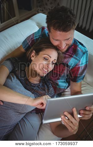 Happy couple using digital tablet in living room at home