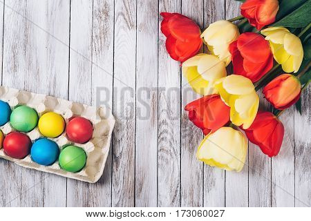 Colored easter eggs and fresh tulips on the white wooden background.