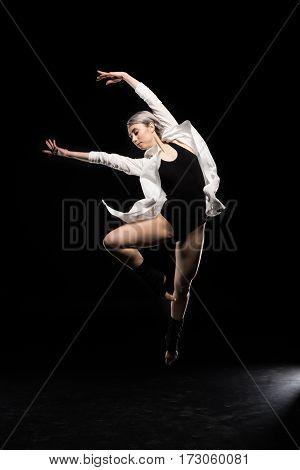 beautiful woman in bodysuit dancing on black