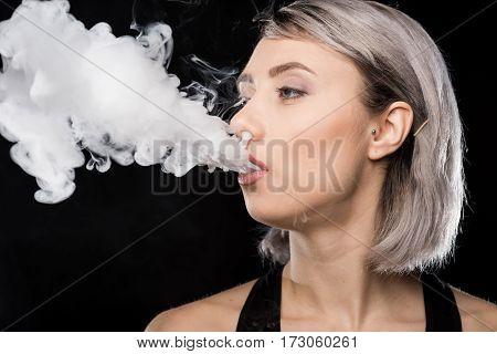 portrait of woman in bodysuit exhaling smoke on black