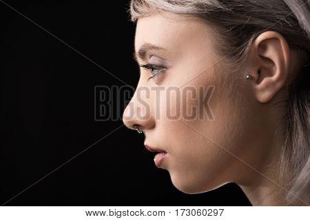 Profile portrait of beautiful young stylish woman on black