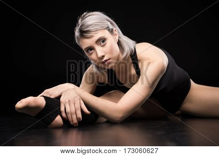 Attractive young sporty woman dancer stretching on black