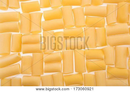 top view of small raw macaroni for making pasta on white