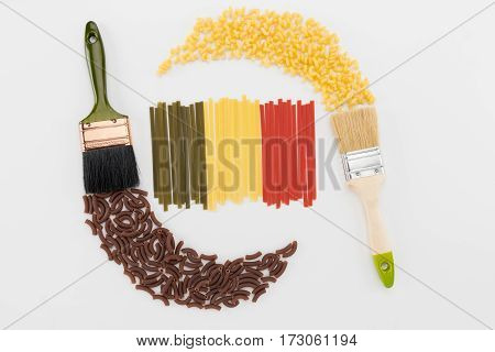 Colorful different types macaroni italian pasta and two brushes on white