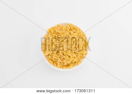 Top view of plate with small raw italian macaroni