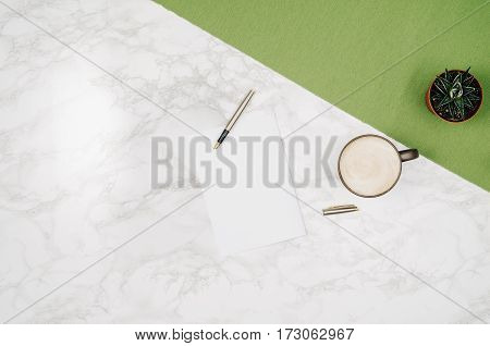 Blank notebook page on white marble table background. Image taken from above, top view. Frame composition with copy space