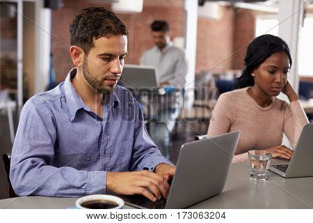 Businesspeople Working On Laptops In Office Coffee Bar