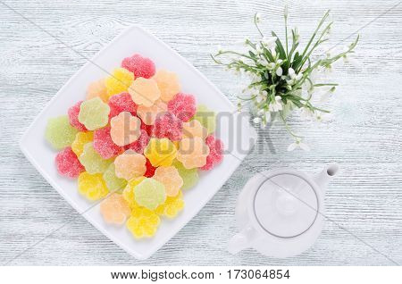 spring snowdrops and dessert fruit candy with coffee pot from top on vintage wooden background