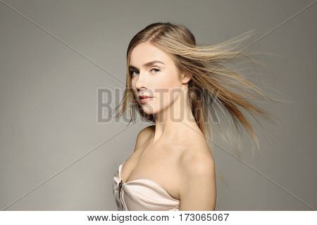 Beautiful young woman with long straight hair on color background
