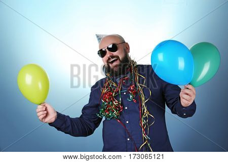 Funny fat man with birthday hat and balloons on color background
