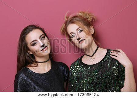 Beautiful young women with cat makeup on color background